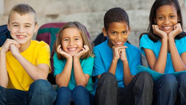 cheerful primary school children sitting outdoors